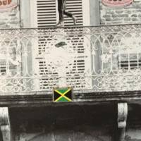 Collage of building with ornate double doors, Bob Marley and an unknown black man in the foreground with two cats and a goldfish in a bowl, other small items include the Jamaican flag, a dollar bill, Campbell's soup cans